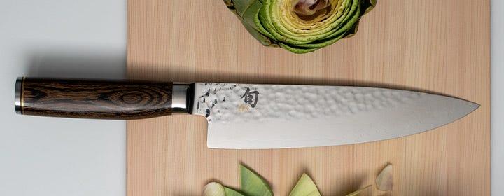 Shun Premier Chef's knife on hinoki cutting board with artichokes